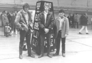 Left to Right: Ed Weninger, Jim Morgan, and Brent Berger stand in front of Daktronics' first Matside three-sided wrestling scoreboard in 1971.
